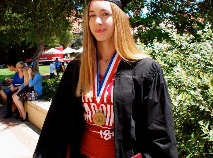 Student in cap and gown with medal.